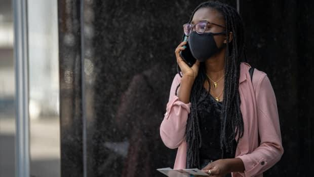A woman wearing a mask makes a phone call in Ottawa on April 6, 2021. (Andrew Lee/CBC - image credit)
