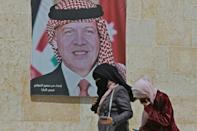 Women walk past a poster of Jordan's King Abdullah II on a street in the capital Amman on Tuesday