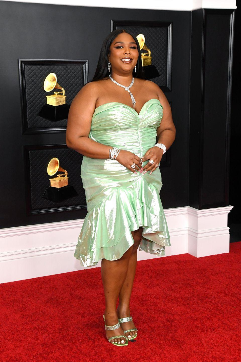<p>Lizzo opted for a strapless, metallic green midi dress by Balmain for the 2021 Grammys, which was complete with a mermaid-inspired ruffled hem. She later changed into a floor-length, pink version of the frock as she presented on stage.</p>