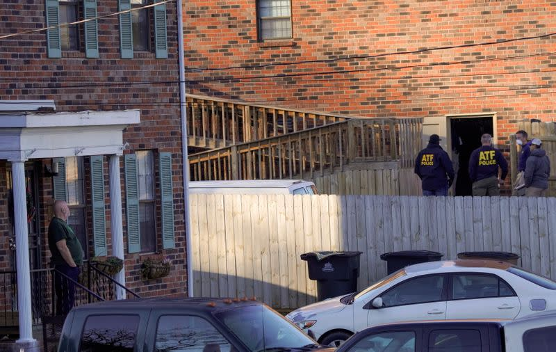 A neighbor watches as Law enforcement officers gather to investigate information arising the day after a downtown Nashville explosion, outside a duplex house in Antioch