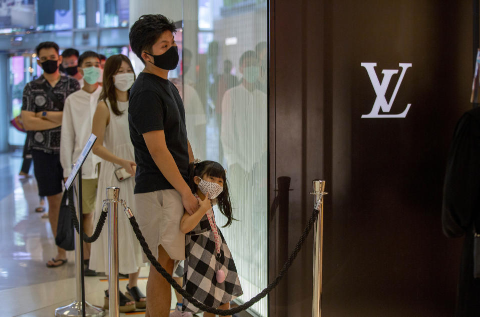 Patrons stand in a line to enter the Louis Vuitton shop at the upmarket shopping mall Siam Paragon in Bangkok, Thailand, Sunday, May 17, 2020. Thai authorities allowed department stores, shopping malls and other businesses to reopen from Sunday, selectively easing restrictions meant to combat the coronavirus. (AP Photo/ Gemunu Amarasinghe)