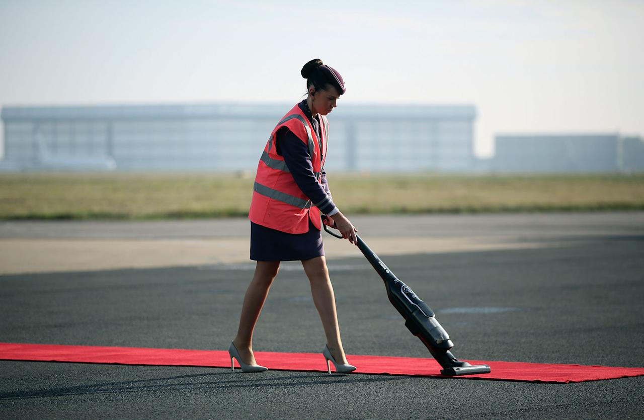 <p>A worker vacuums the red carpet before the arrival of Colombian President Juan Manuel Santos and his wife, Maria Clemencia de Santos, at Stansted airport in Stansted, England, Oct. 31, 2016. (Neil Hall/Reuters) </p>