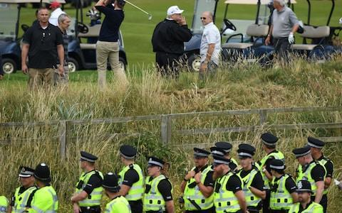 <span>Police secure the area as U.S. President Donald Trump, wearing a hat with Trump and USA displayed on it, plays golf at Trump Turnberry Luxury Collection Resort during the President's first official visit to the United Kingdom</span> <span>Credit: Getty Images </span>