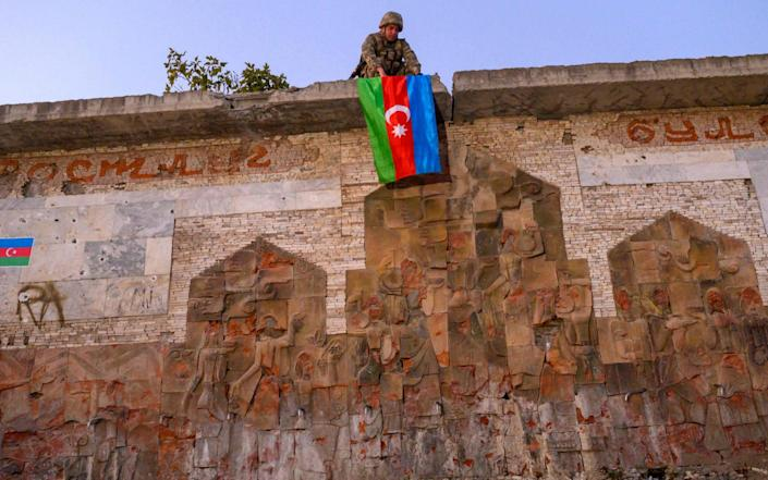 An Azeri soldier hangs the flag of Azerbaijan in the city of Jabrayil, where Azeri forces regained control during the fighting with Armenia over the breakaway region of Nagorno-Karabakh on October 16, 2020. - AFP/An Azeri soldier hangs the flag of Azerbaijan in the city of Jabrayil, where Azeri forces regained control during the fighting with Armenia over the breakaway region of Nagorno-Karabakh on October 16, 2020.