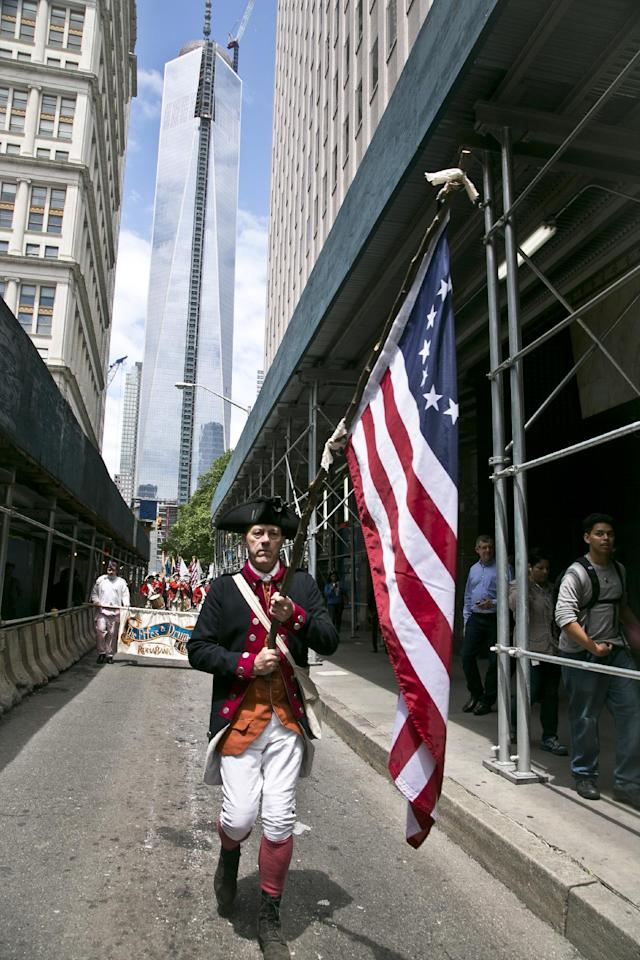 "With the new WorldTrade Center tower as a backdrop, a flag bearer in American revolutionary costume leads the ""Old Barracks Fife and Drum Corps,"" from Trenton, N.J., in a Flag Day procession along Fulton Street on Friday, June 14, 2013 in New York. (AP Photo/Bebeto Matthews)"