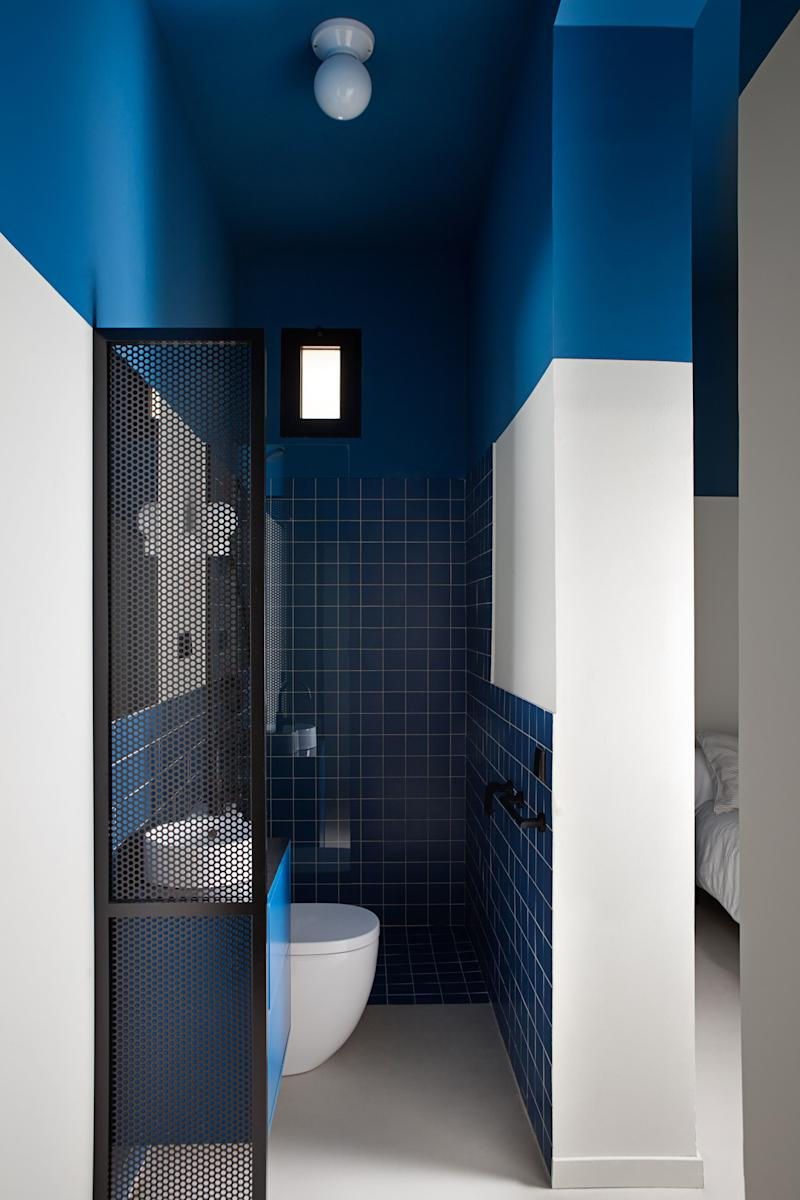 After: In the blue and beige room's adjoining bathroom, a bold painted ceiling makes the space appear much taller. Next to the sink, Ana and Enrique added a sliver of mesh to create some privacy without blocking the precious natural light coming from the bedroom window.
