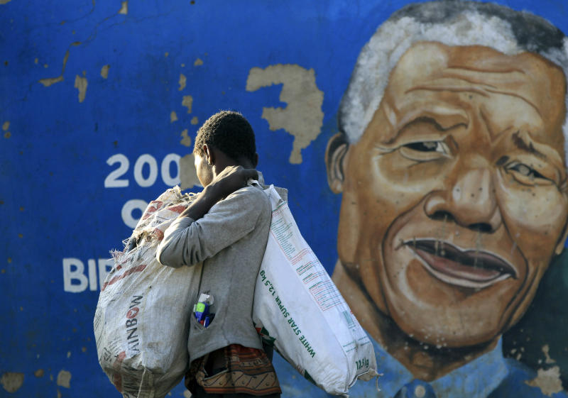 """Thabiso Ndandwe walks in front of a mural of former South African President Nelson Mandela in a Soweto township, in Johannesburg, South Africa, Monday, June 10, 2013. Mandela was in serious but stable condition in a Pretoria hospital for the third day Monday with a recurring lung infection, and a foundation led by retired archbishop Desmond Tutu described the 94-year-old anti-apartheid hero as an """"extraordinary gift"""" to South Africa. (AP Photo/Themba Hadebe)"""