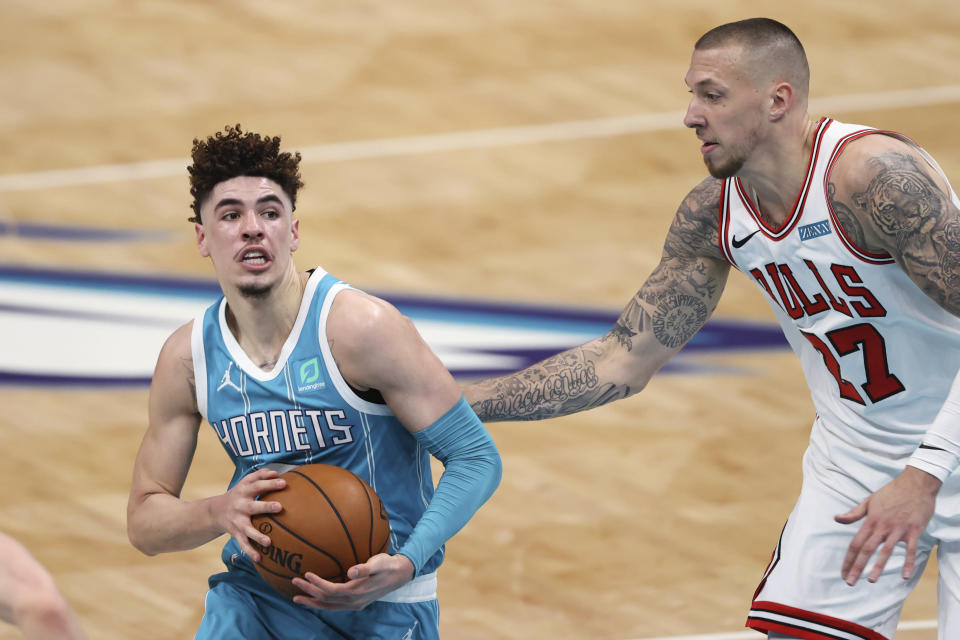 Charlotte Hornets guard LaMelo Ball, left, drives to the basket next to Chicago Bulls center Daniel Theis during the first half of an NBA basketball game in Charlotte, N.C., Thursday, May 6, 2021. (AP Photo/Nell Redmond)