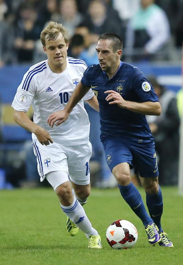 France's Franck Ribery, right, dribbles Teemu Pukki of Finland during their 2014 World Cup Group I qualifying soccer match at the Stade de France stadium in Saint Denis, north of Paris, France, Tuesday, Oct. 15, 2013. (AP Photo/Francois Mori)