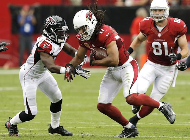 Arizona Cardinals wide receiver Larry Fitzgerald, center, makes a catch as Atlanta Falcons cornerback Desmond Trufant, left, pursues during the first half of an NFL football game Sunday, Oct. 27, 2013, in Glendale, Ariz. (AP Photo/Rick Scuteri)