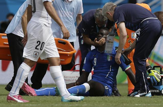 Italy's Mario Balotelli receives assistance during the group D World Cup soccer match between Italy and Uruguay at the Arena das Dunas in Natal, Brazil, Tuesday, June 24, 2014. (AP Photo/Andrew Medichini)