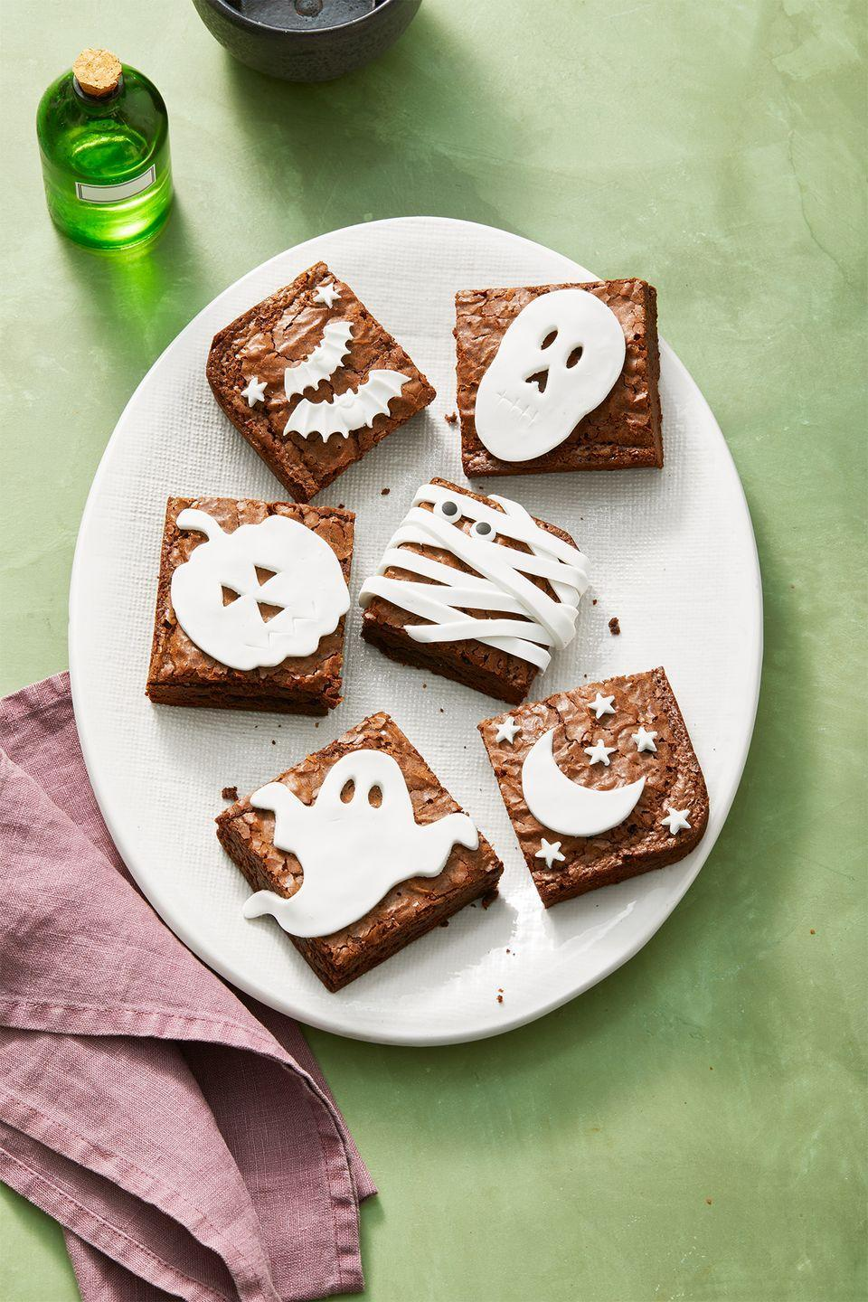 """<p>Need a last-minute dessert for your Halloween party? Decorate brownies (homemade or store-bought!) with cut-out white fondant.</p><p><strong>RELATED: </strong><a href=""""https://www.goodhousekeeping.com/holidays/halloween-ideas/g565/halloween-party-ideas/"""" rel=""""nofollow noopener"""" target=""""_blank"""" data-ylk=""""slk:80 Fun and Creepy Ideas for a Halloween Party to Remember"""" class=""""link rapid-noclick-resp"""">80 Fun and Creepy Ideas for a Halloween Party to Remember</a></p>"""