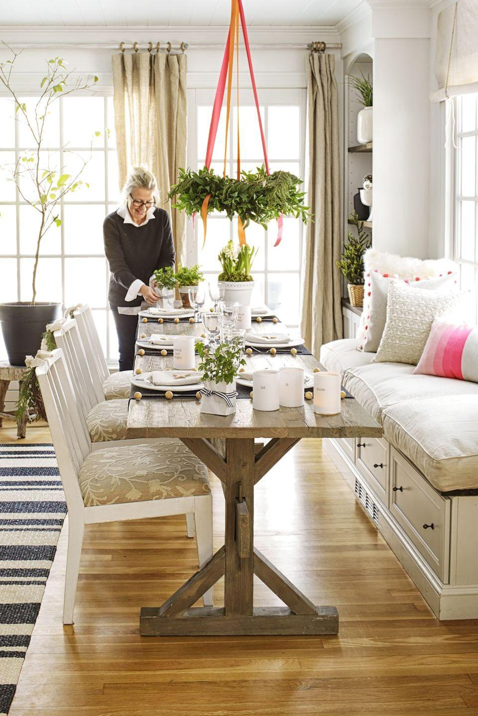 """<p>Using a hook and ribbon, suspend greens from the ceiling above your table. Love the look, but have a permanent light fixture? Drape pine around the frame and secure with ribbon.</p><p><span class=""""redactor-invisible-space""""><a class=""""link rapid-noclick-resp"""" href=""""https://go.redirectingat.com?id=74968X1596630&url=https%3A%2F%2Fwww.etsy.com%2Flisting%2F240787306%2Fpreserved-boxwood-wreathall&sref=https%3A%2F%2Fwww.goodhousekeeping.com%2Fholidays%2Fchristmas-ideas%2Fhow-to%2Fg2196%2Fchristmas-table-settings%2F"""" rel=""""nofollow noopener"""" target=""""_blank"""" data-ylk=""""slk:SHOP WREATHS"""">SHOP WREATHS</a> </span><br></p>"""