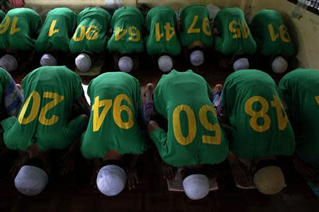 Rohingya Muslim illegal immigrants pray at the Immigration Detention Centre during the Muslim holy fasting month of Ramadan in Kanchanaburi province, in this file picture taken July 10, 2013. REUTERS/Athit Perawongmetha/Files