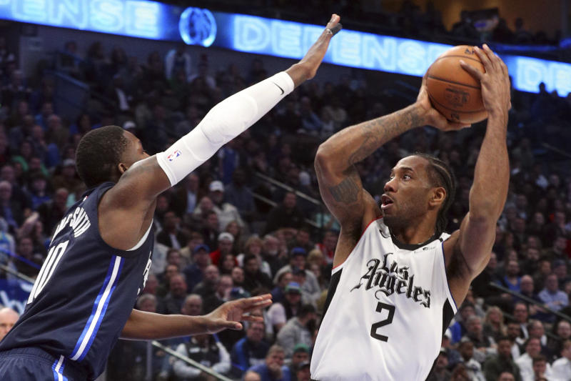 Dallas Mavericks forward Dorian Finney-Smith (10) tries to defend against a shot by Los Angeles Clippers forward Kawhi Leonard (2) during the second half of an NBA basketball game Tuesday, Jan. 21, 2020 in Dallas. (AP Photo/Richard W. Rodriguez)