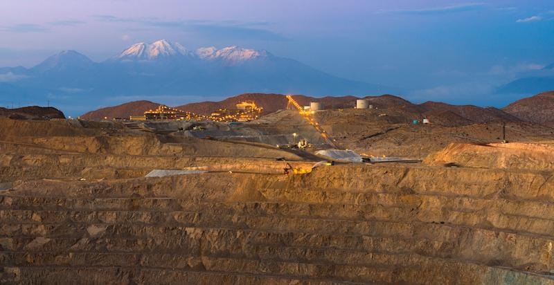 Open pit mine near sunset with light-up equipment and mountains in background.
