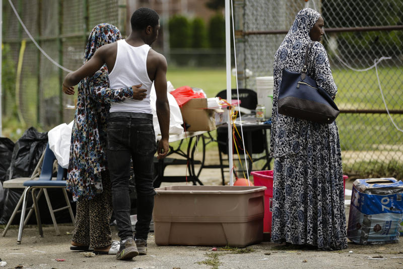 A person looks for items left behind after a shooting at a graduation party in Philadelphia, Monday, June 17, 2019. Authorities say at least one man has been killed and multiple other people were wounded in the shooting which occurred around 10 p.m. Sunday. (AP Photo/Matt Rourke)