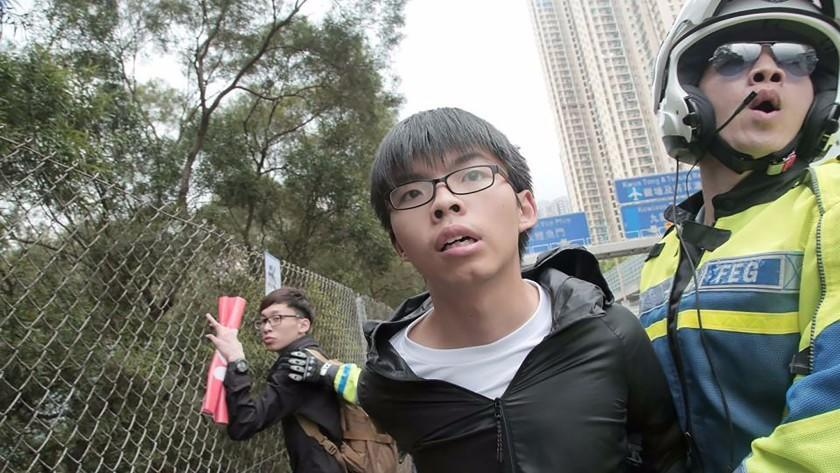 This handout photo released by Demosisto shows Hong Kong pro-democracy activist and leader of political party Demosisto, Joshua Wong, being detained by a police officer after he and others ran onto a road in Hong Kong on May 19, 2016.