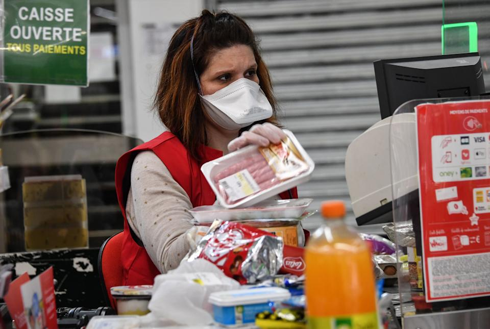 A cashier works wearing a face mask in a supermarket in Montpellier, in the southern France, on March 30, 2020, on the fourteenth day of a lockdown in France to stop the spread of the epidemic COVID-19, caused by the novel coronavirus. (Photo by Pascal GUYOT / AFP) (Photo by PASCAL GUYOT/AFP via Getty Images)