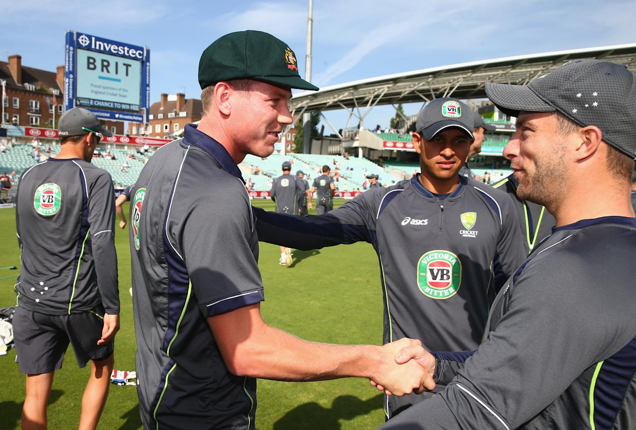LONDON, ENGLAND - AUGUST 21:  James Faulkner of Australia is congratulated by Usman Khawaja of Australia and Matthew Wade of Australia after being presented with his Baggy Green Cap before making his test debut during day one of the 5th Investec Ashes Test match between England and Australia at the Kia Oval on August 21, 2013 in London, England.  (Photo by Ryan Pierse/Getty Images)