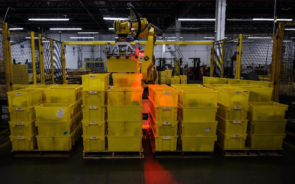 E-commerce titan Amazon has deployed some of the most advanced instruments in the rapidly growing field of robots capable of collaborating with humans (AFP Photo/Johannes EISELE)