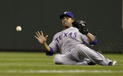 Texas Rangers right fielder Nelson Cruz slides toward a fly ball from Seattle Mariners' Jesus Montero in the eighth inning of a baseball game Thursday, April 11, 2013, in Seattle. Montero doubled on the play. (AP Photo/Elaine Thompson)