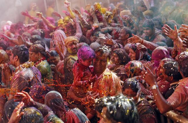 Hindu devotees react as priests (unseen) throw coloured water on them during Holi celebrations at the Bankey Bihari temple in Vrindavan, in the northern Indian state of Uttar Pradesh, March 13, 2014. Holi, also known as the Festival of Colours, heralds the beginning of spring and is celebrated all over India. REUTERS/Anindito Mukherjee (INDIA - Tags: RELIGION SOCIETY TPX IMAGES OF THE DAY)