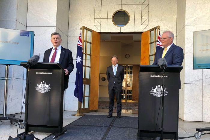 Three men stand in a courtyard with two lecterns