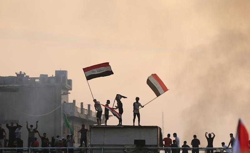 Demonstrators hold Iraqi flags