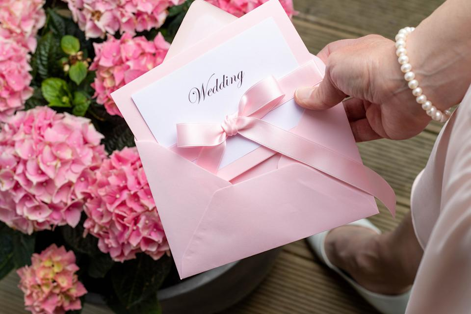 A female hand holding a wedding invitation in a pink envelope. Pink flowers in the background and part of the woman's shoes and dress.