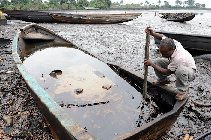 A man in Nigeria's Ogoniland region looks at a mix of oil and water in a boat on the Bodo waterways, heavily polluted by oil spills attributed to Shell in 2011 (AFP Photo/Pius Utomi Ekpei)
