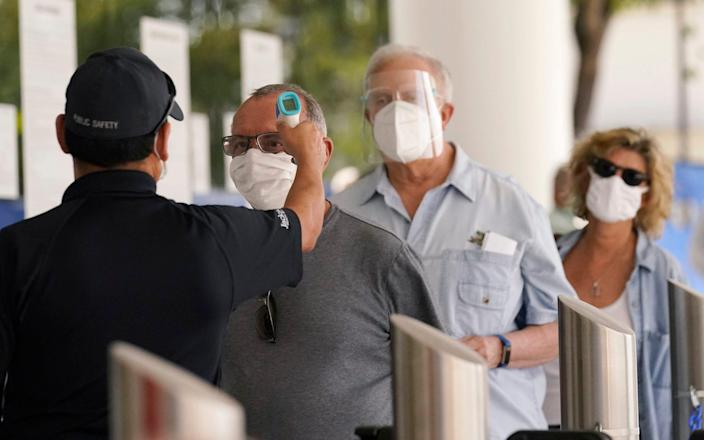 Florida seniors have their temperatures taken before receiving the second dose of the Pfizer vaccine - Marta Lavandier/AP