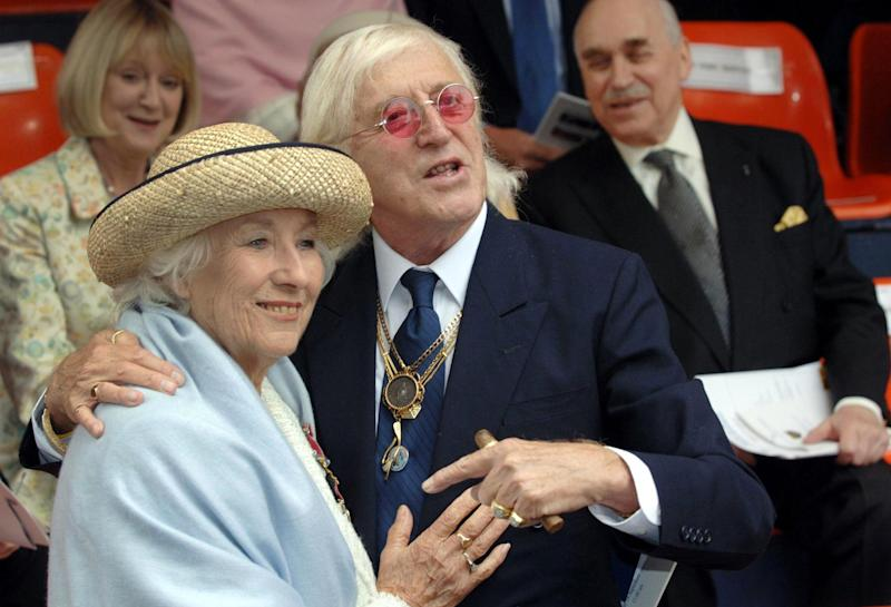 FILE In this Sunday Sept. 18, 2005 file photo British singer Vera Lynn and Jimmy Saville, right are seen at the unveiling of a contemporary sculpture at Victoria Embankment in central London to mark the 65th anniversary of the Battle of Britain.  For decades, Jimmy Savile was a fixture on British television — an eccentric, aggressively jocular host of children's shows and a tireless charity fundraiser. A year after he died, aged 84 and honored as Sir Jimmy, several women have come forward to claim he was also a sexual predator and serial abuser of underage girls. The allegations have set off ripples of shock — but not of surprise. There had, colleagues said, long been rumors. The main question being asked now is: Why did no one do anything?  (AP Photo/Matthew Fearn, Pool, File)