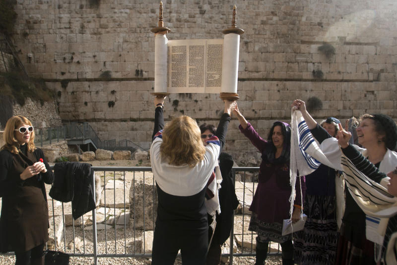 Israeli women of the Women of the Wall organization hold a Torah scroll during a prayer just outside the Western Wall, the holiest site where Jews can pray in Jerusalem's old city, Friday, Dec. 14, 2012. Security guards at the Western Wall, the holiest place where Jews can pray, usually search worshippers for weapons upon entering. But on Friday, they were on the lookout for a seemingly inoffensive possession: Jewish prayer shawls. The shawls are ubiquitous at the holy site, and under Orthodox tradition, are worn only by men. When several dozen women draped in them attempted to enter the area, their multicolored garments were confiscated. (AP Photo/Dan Balilty)