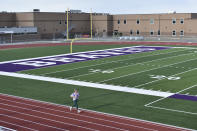 In this Wednesday, May 19, 2021, photo, Mallory Wilson runs on the track at Parshall High School on the Fort Berthold Indian Reservation in Parshall, North Dakota. About half of the 16,000 members live on the Fort Berthold Indian Reservation atop one of the biggest U.S. oil discoveries in decades, North Dakota's Bakken shale formation. The drilling rush has brought the tribes unimagined wealth, $1.4 billion and counting, and they hope it will last another 20 to 25 years. (AP Photo/Matthew Brown)