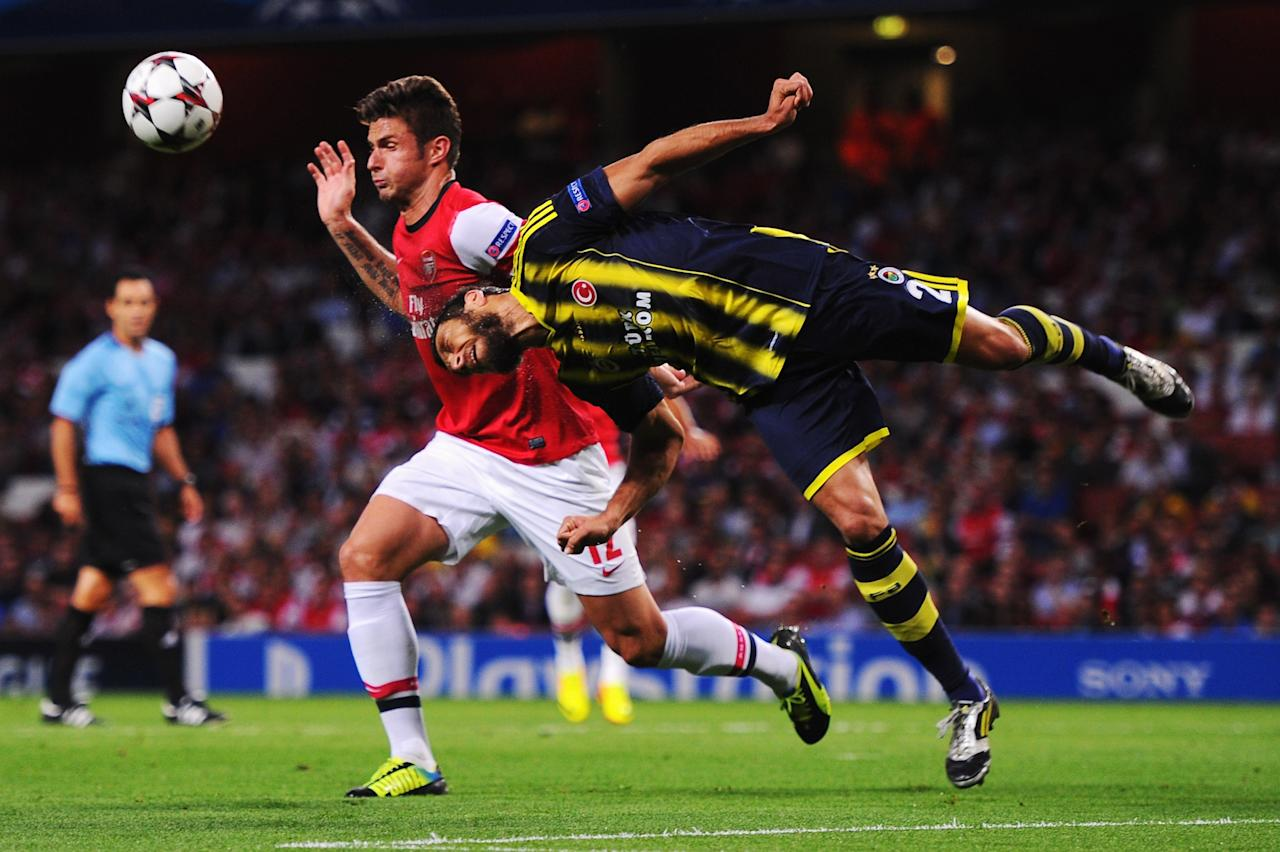 LONDON, ENGLAND - AUGUST 27: (L-R) Olivier Giroud of Arsenal is challenged by Egemen Korkmaz of Fenerbahce during the UEFA Champions League Play Off Second leg match between Arsenal FC and Fenerbahce SK at Emirates Stadium on August 27, 2013 in London, England. (Photo by Michael Regan/Getty Images)