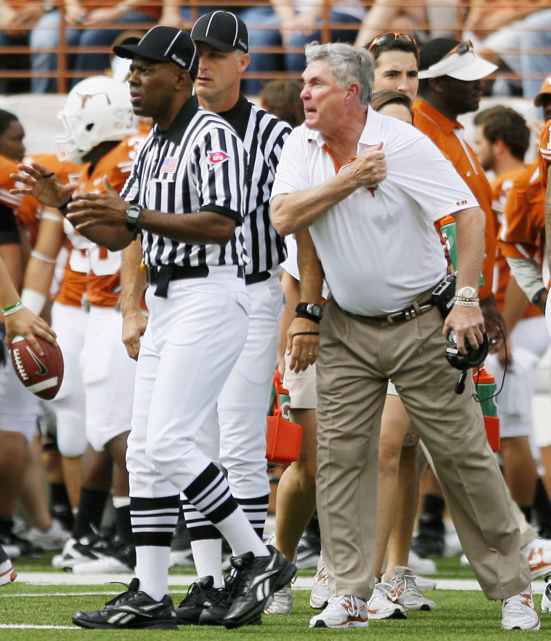 FILE - This Oct. 23, 2010 file photo shows Texas head coach Mack Brown, right, complaining to officials during the first half of an NCAA college football game against Iowa State, in Austin, Tx.  Losing to Iowa State was the low point for the 2010 Texas Longhorns. (AP Photo/Darren Abate, File)