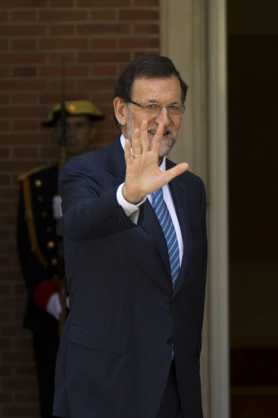 Spain's Prime Minister Mariano Rajoy waves during a welcome ceremony for Romania's Prime Minister Victor Ponta, not seen, before a meeting at the Moncloa Palace, in Madrid, Monday, July 22, 2013. Opposition leaders called for Rajoy to explain himself before Parliament or face a censure vote. Rajoy brushed off demands he should resign after text messages emerged showing him comforting a former political party treasurer under investigation over a slush fund and secret Swiss bank accounts. The treasurer has claimed Rajoy took under-the-counter payments, accusations denied by Rajoy. (AP Photo/Daniel Ochoa de Olza)