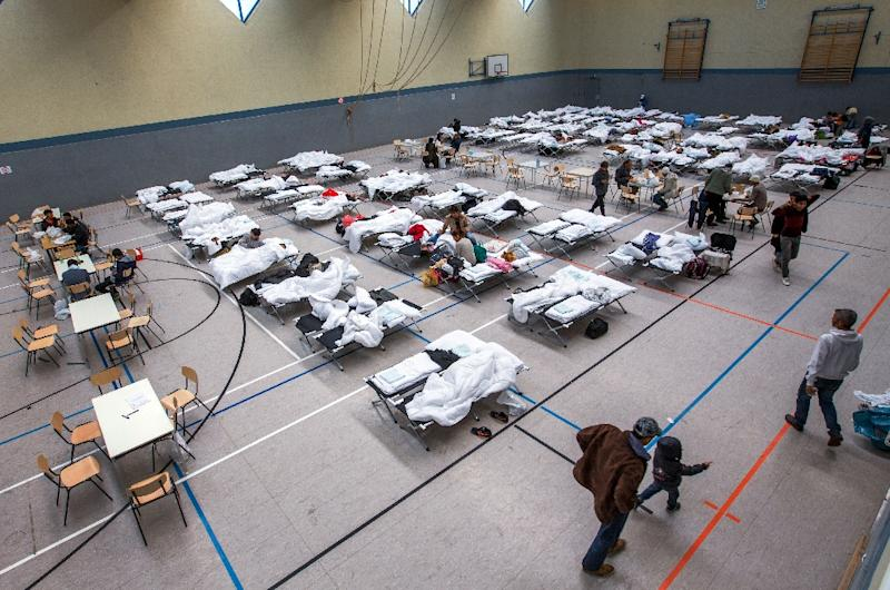 Migrants walk next to camp beds in a makeshift refugee shelter in a gym in Stern-Buchholz, northern Germany, on September 7, 2015 (AFP Photo/Jens Buttner)