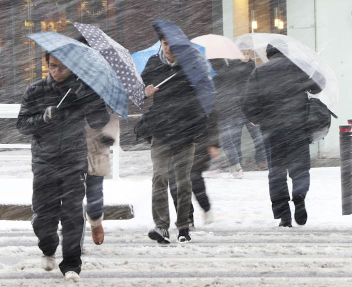 People walk against blowing snow in Tokyo, Saturday, Feb. 8, 2014. The Japan Meteorological Agency issued Saturday the first heavy snowfall warning for central Tokyo in 13 years. (AP Photo/Koji Sasahara)