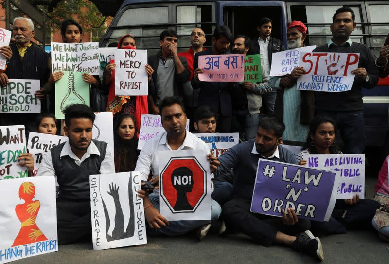 People hold placards and shout slogans as they take part in a protest against the alleged rape and murder of a 27-year-old woman on the outskirts of Hyderabad, in New Delhi