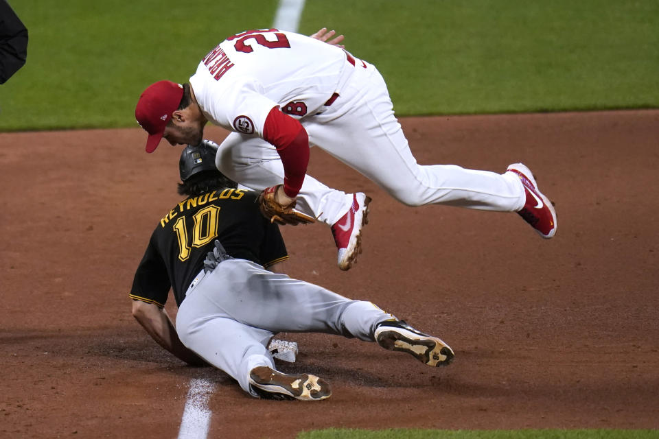 Pittsburgh Pirates' Bryan Reynolds dives safely back to third to avoid the tag from St. Louis Cardinals third baseman Nolan Arenado during the sixth inning of a baseball game Tuesday, May 18, 2021, in St. Louis. (AP Photo/Jeff Roberson)