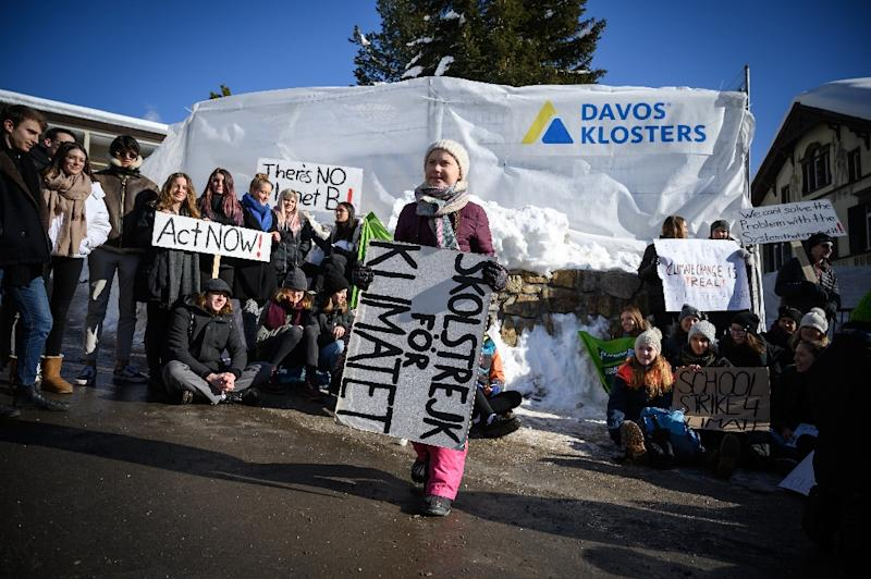 "Greta Thunberg (C) holds a placard next to students during a ""School strike for climate"" held on the sidelines of the World Economic Forum (WEF) on Friday (AFP Photo/Fabrice COFFRINI)"
