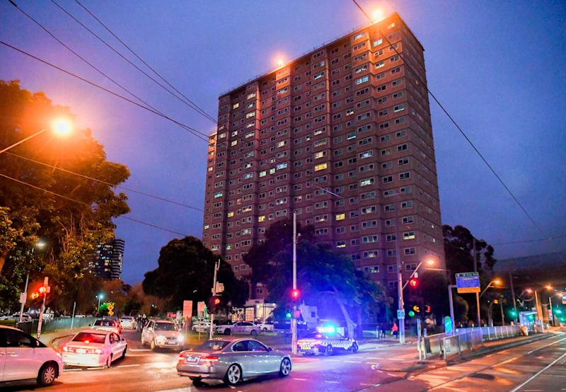 Police vehicles park outside one of nine public housing estates which have been locked down in Melbourne on July 4 (Photo: WILLIAM WEST via Getty Images)