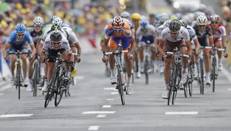 Mark Cavendish of Britain, left, sprints towards the finish line as he catches up with breakaway Luis-Leon Sanchez of Spain, center in orange, to win the 18th stage of the Tour de France cycling race over 222.5 kilometers (138.3 miles) with start in Blagnac and finish in Brive-la-Gaillarde, France, Friday July 20, 2012. (AP Photo/Laurent Rebours)