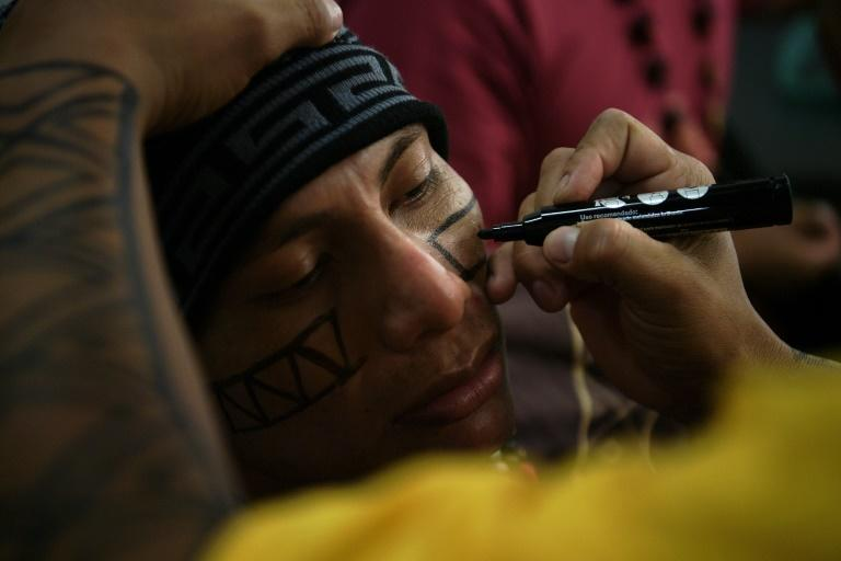 Bro MC member Kelvin Peixoto has traditional markings applied to his face with a marker ahead of a show in Rio de Janeiro