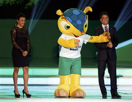 Brazil's women's team soccer player Marta (L) and former player Bebeto smile on stage with the World Cup mascot Fuleco during the draw for the 2014 World Cup at the Costa do Sauipe resort in Sao Joao da Mata, Bahia state, December 6, 2013. REUTERS/Sergio Moraes