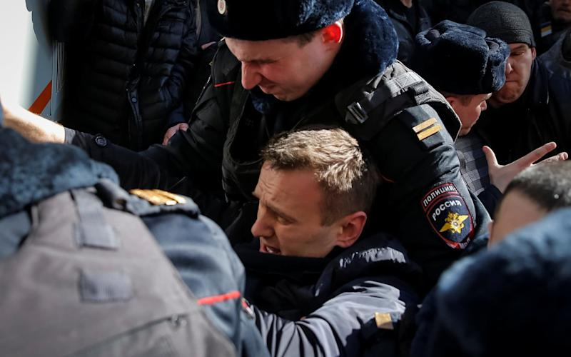 Police officers detain anti-corruption campaigner and opposition figure Alexei Navalny