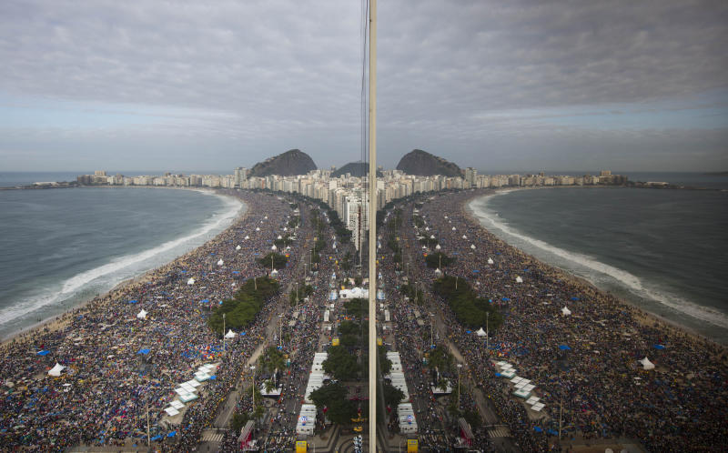 In this July 28, 2013 file photo, people gathering on the shore of Copacabana beach are reflected on a beachfront hotel window, before the arrival of Pope Francis for the World Youth Day's closing Mass, in Rio de Janeiro, Brazil. Brazilian researchers say the Roman Catholic Church's 3.7 million estimate of the crowd that turned out to see Francis celebrate Mass on Copacabana beach is inflated, if still impressive. One of Brazil's top polling and research firms estimates the crowd at the Mass was at most 1.5 million people. (AP Photo/Felipe Dana, File)