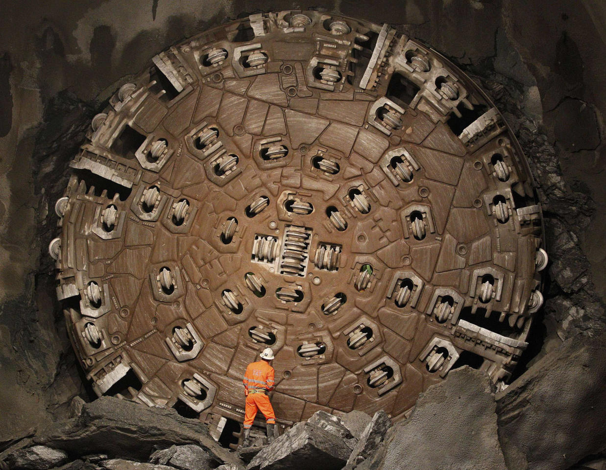 A miner stands in front of the drill machine 'Sissi' after it broke through the rock at the final section Faido-Sedrun, at the construction site of the NEAT Gotthard Base Tunnel Friday Oct. 15, 2010. With a length of 57 km (35 miles) crossing the Alps, the world's longest train tunnel should become operational at the end of 2017.
